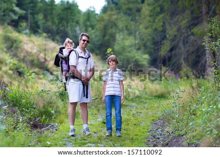 Happy young family, active father, his son and a baby daughter hiking in a beautiful autumn forest - stock photo