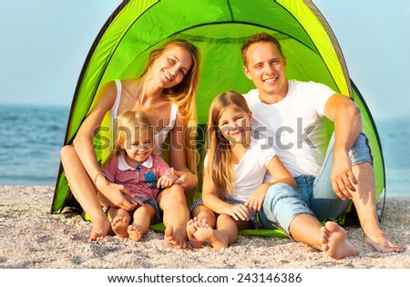 Happy young family camping on the beach. Summertime - stock photo
