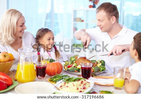 Happy young family celebrating Thanksgiving by festive table - stock photo