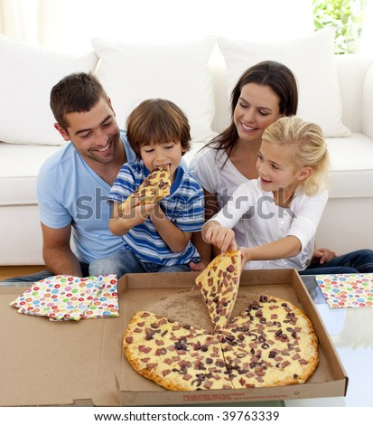 Happy young family eating pizza in living-room all together - stock photo