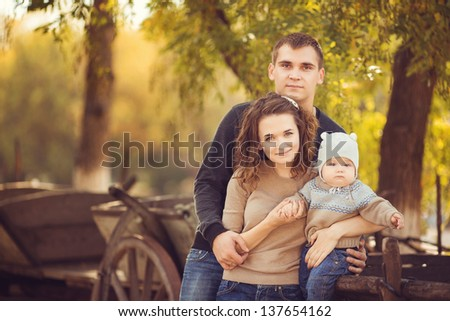 Happy young family enjoying the summer in park. Outdoors. - stock photo