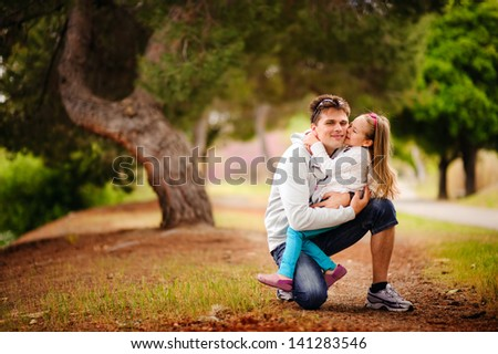 happy young family father and baby daughter hugging and smiling at beautiful park in summer day - stock photo