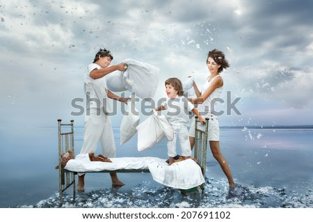 Happy young family fight a battle by pillows on a bed in the sea - stock photo