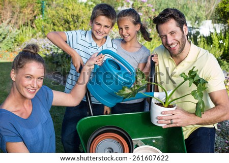 Happy young family gardening together in the garden - stock photo