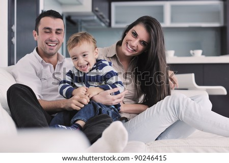 happy young family have fun and relaxing at new home with bright furniture - stock photo