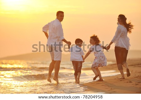 happy young family have fun on beach run and jump  at sunset - stock photo