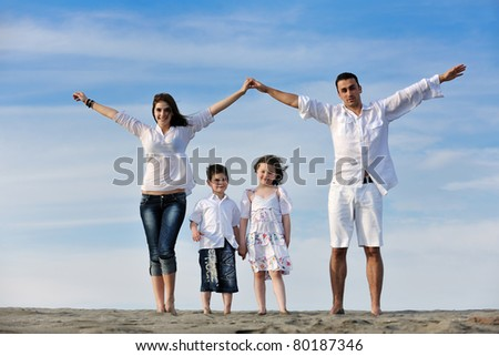happy young family have fun on beachand showing home sign with conncected hands while protecting childrens