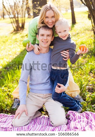 happy young family having a picnic in the park on a summer day  (focus on the man) - stock photo