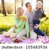 happy young family having a picnic in the park on a summer day (focus on the woman) - stock photo