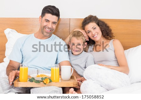 Happy young family having breakfast in bed at home in bedroom - stock photo