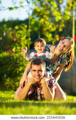 Happy young family having fun outdoors in summer. Mother, father and their cute baby-girl are playing in the sunny garden. Happy parenthood and childhood concept. Focus on the father.