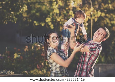 Happy young family having fun outdoors in summer. Mother, father and their cute baby-girl are playing in the sunny garden. Happy parenthood and childhood concept.  - stock photo