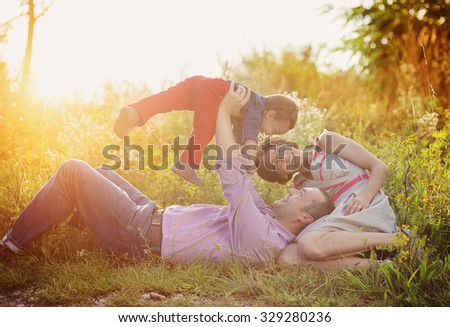 Happy young family having fun outside in summer nature - stock photo