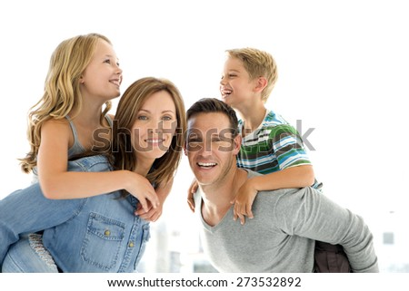 Happy young family having fun. Parents giving piggyback ride to their son and daughter. Horizontal shot over white background. - stock photo