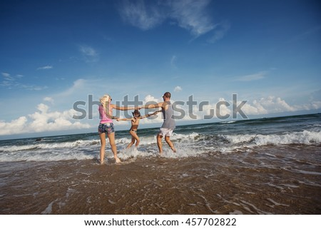 Happy young family having fun running on beautiful beach with waves and sea foam. Family traveling concept - stock photo