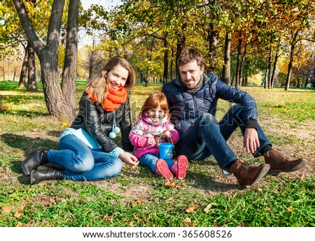 Happy young family in an autumn park - stock photo