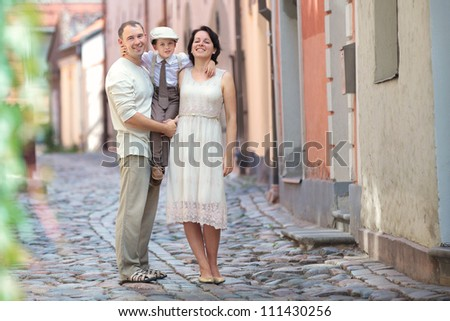 Happy young family in city street - stock photo
