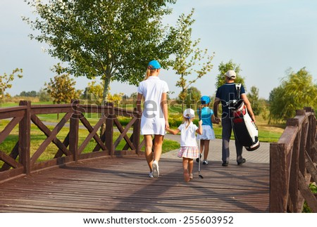 Happy young family in golf country club - stock photo