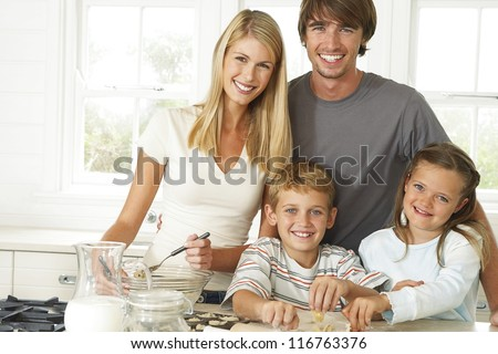 Happy young family in the kitchen with Mum, Dad and their young son and daughter posing together while baking cookies - stock photo