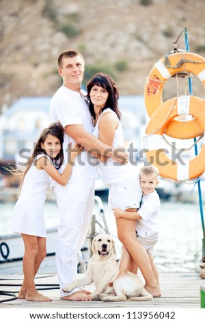 Happy young family in white clothing have fun and play with beautiful dog at vacations  on berth in summer