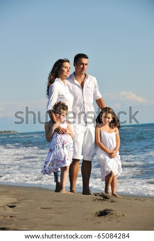 happy young family in white clothing have fun at vacations on beautiful beach - stock photo