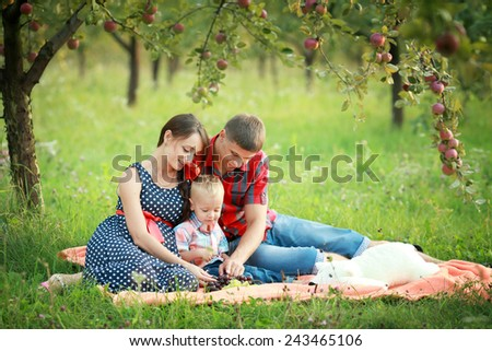 Happy young family is having fun in the green summer park outdoo - stock photo