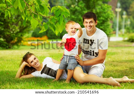 Happy young family is having fun in the green summer park outdoors on a sunny day. Mother, father and their little baby-boy are walking in the park. Love and family concept. - stock photo