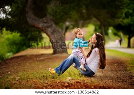 happy young family mother and baby daughter hugging and walking at beautiful park