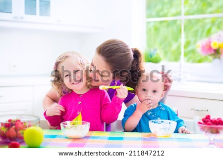 Happy young family, mother with two children, adorable toddler girl and funny messy baby boy having healthy breakfast eating fruit and dairy, sitting in a white sunny kitchen with window - stock photo