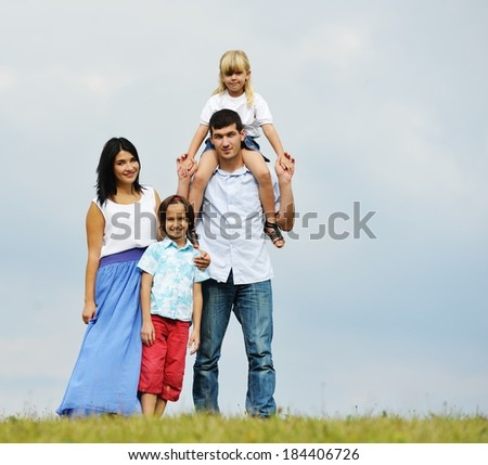 Happy young family of four members on green summer grass meadow having fun