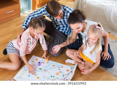 Happy young family of four playing at board game in domestic interior - stock photo