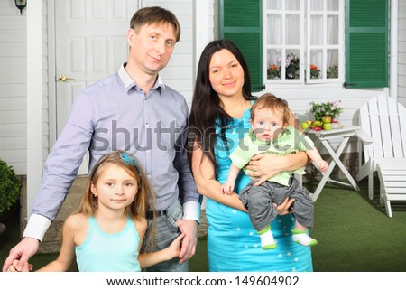 Happy young family of four stand near porch of new their cottage.