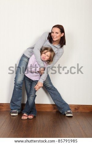 Happy young family of mum and daughter with hug and embrace with big laughing smiles. Both wearing denim jeans and hoodie. - stock photo