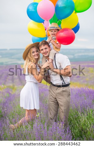 Happy young family of three person walking on lavender field with color balloons