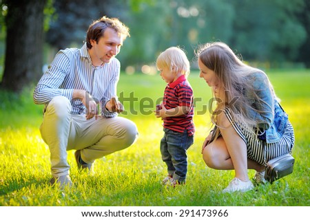 Happy young family of three spending their family time together in the sunny park