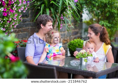 Happy young family, parents with two children, adorable little girl and a funny baby boy, eating lunch in a beautiful outdoor cafe with flowers in a city center on a warm summer day - stock photo