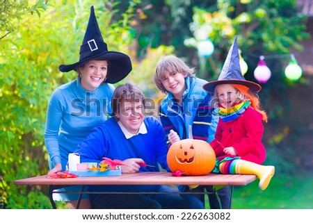 Happy young family, parents with two children, teenager boy and funny toddler girl wearing witch costume and hat celebrating Halloween and pumpkin carving in the garden - stock photo