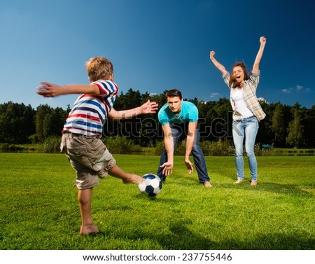 Happy young family playing football outdoors  - stock photo