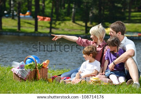 Happy young  family playing together with kids and eat healthy food  in a picnic outdoors