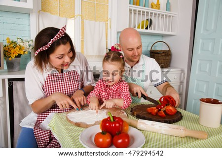 Happy young family preparing dinner in the kitchen