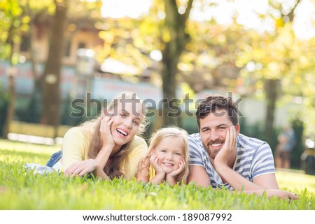 Happy young family resting in the park - stock photo