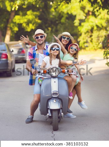 Happy young family riding a vintage scooter in the street wearing hats and sunglasses. Holiday and travel concept - stock photo