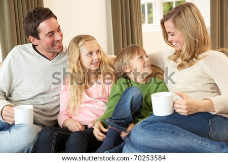 Happy young family sitting and talking on sofa - stock photo