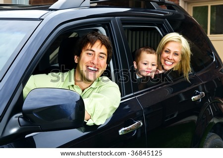 Happy young family sitting in black car looking out windows - stock photo