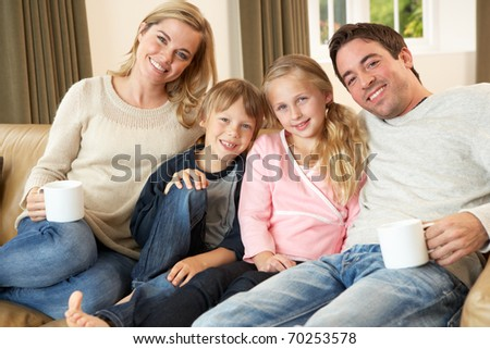 Happy young family sitting on sofa holding cups - stock photo