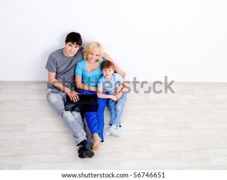 Happy young family sitting with laptop on the floor in empty room  together - high angle