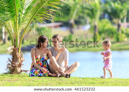 happy young family spending time in a tropical garden on a summer day