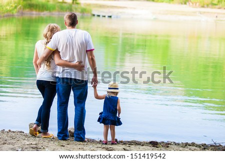 happy young family spending time outdoor on a lake - stock photo