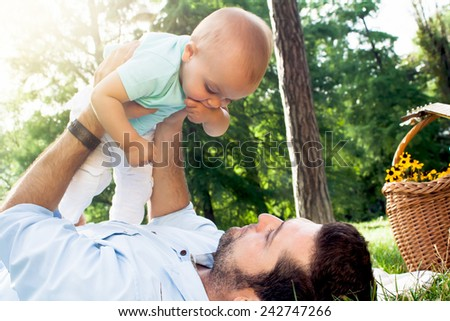Happy young family spending time outdoor on a summer day. Father and son.