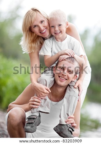 happy young family spending time outdoor on a summer day (focus on the man) - stock photo